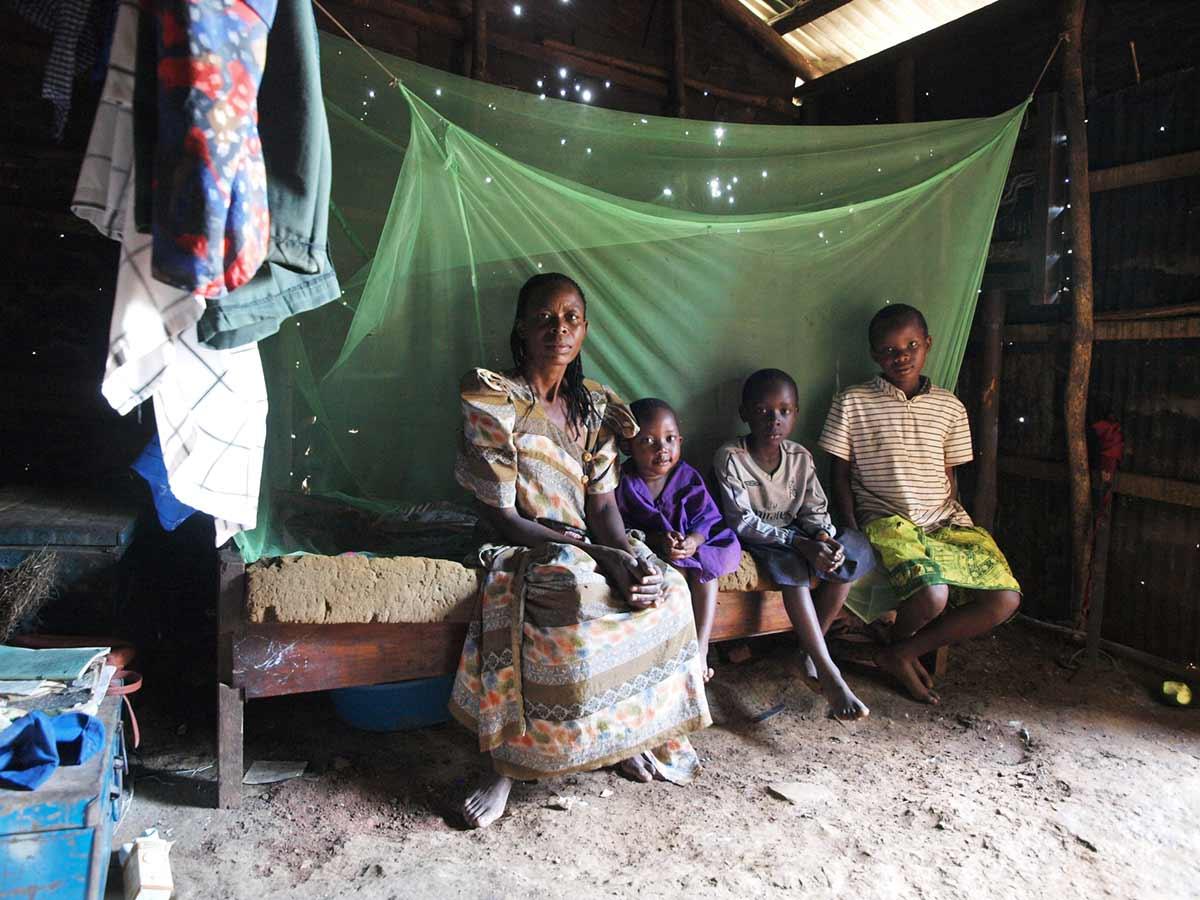 """""""Anyopa Abisagi, rechts im Bild, lebte von 2005 bis 2008 im St. Moses Center, jetzt reintegriert. Das Schuldgeld wird vom St. Moses Center weiterhin übernommen. Sie wohnt hier mit ihrer Mutter und 2 Geschwistern. Ein Moskitonetz ist nicht selbstverträglich."""" - Mandy Knuth"""