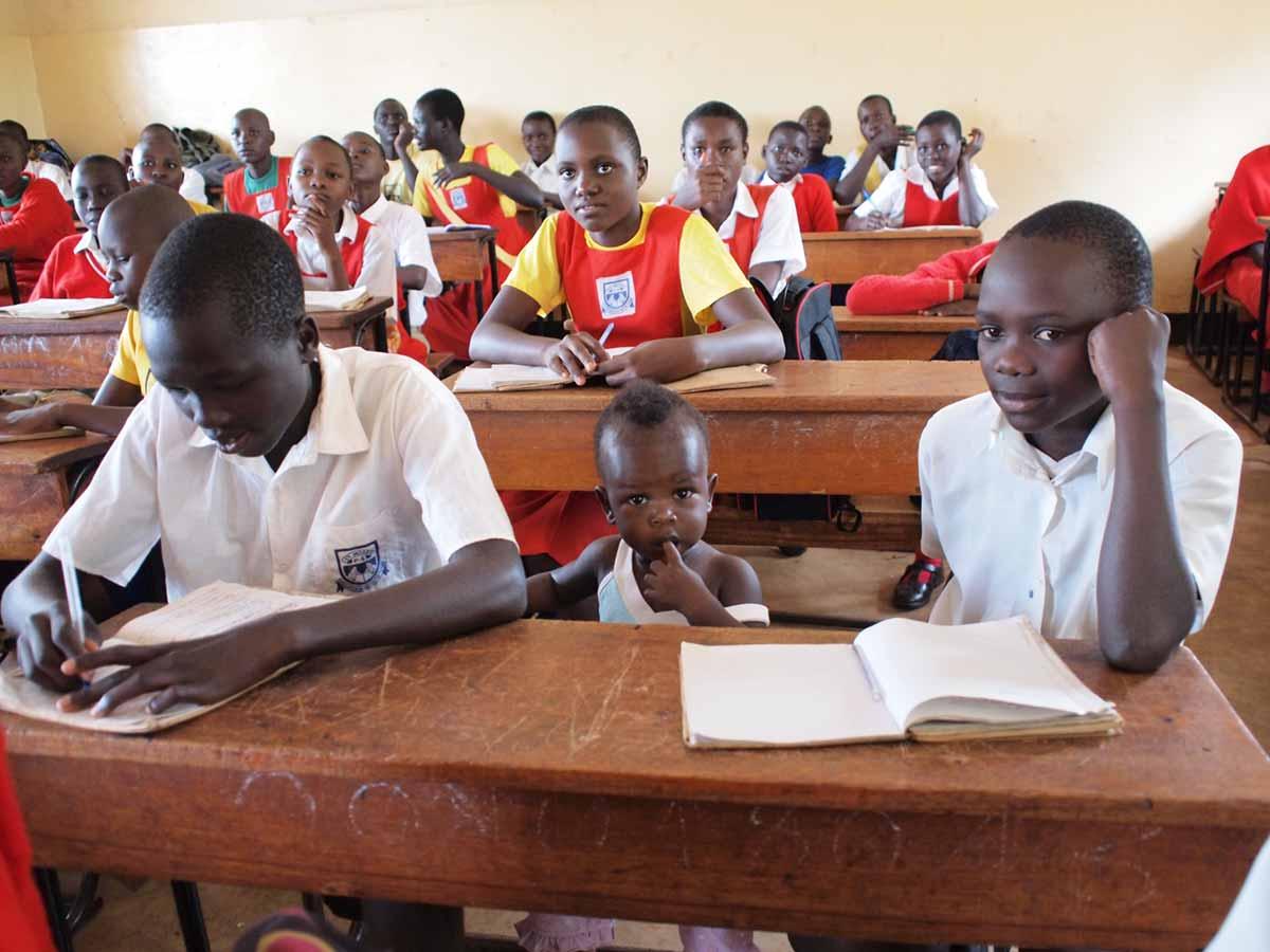 """""""In der Schule sind oft bis zu 100 Schüler in einer Klasse. Dieses kleine Mädchen wird von ihren Geschwistern mitgenommen, weil es sonst tagsüber allein im Dorf bleiben muss da die Eltern verstorben sind. »Hier ist es sicherer«, erzählte mir die Lehrerin."""" – Mandy Knuth"""