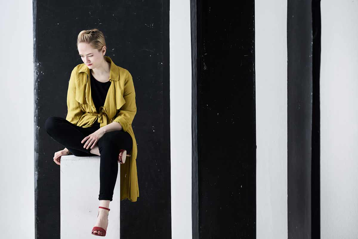 kaupo-kikkas-lady-sits-on-a-plinth-in-front-of-vertically-striped-backdrop