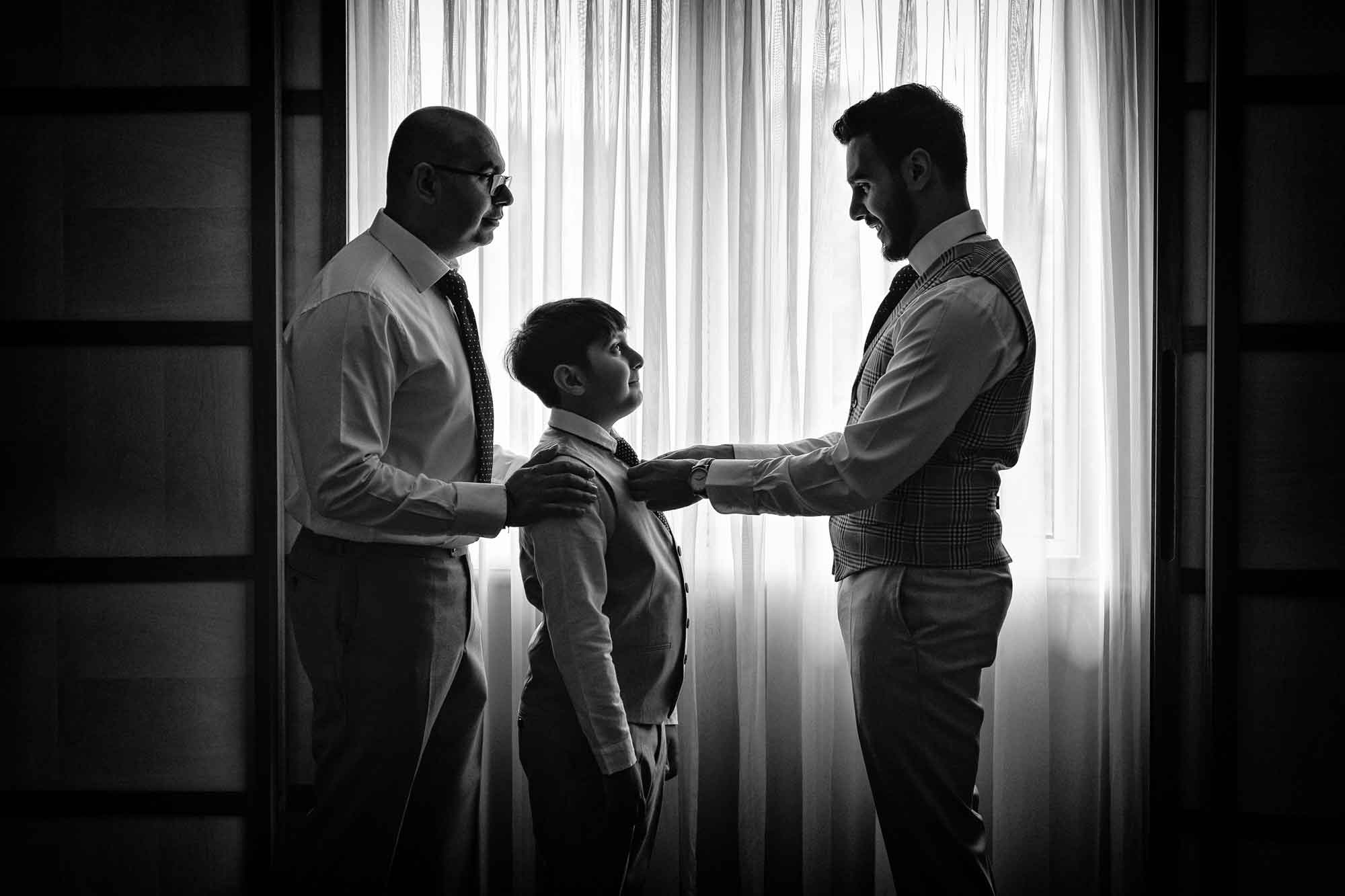 kate-hopewell-smith-sony-alpha-9-groom-adjusts-page-boy-tie-before-ceremony-as-father-looks-on